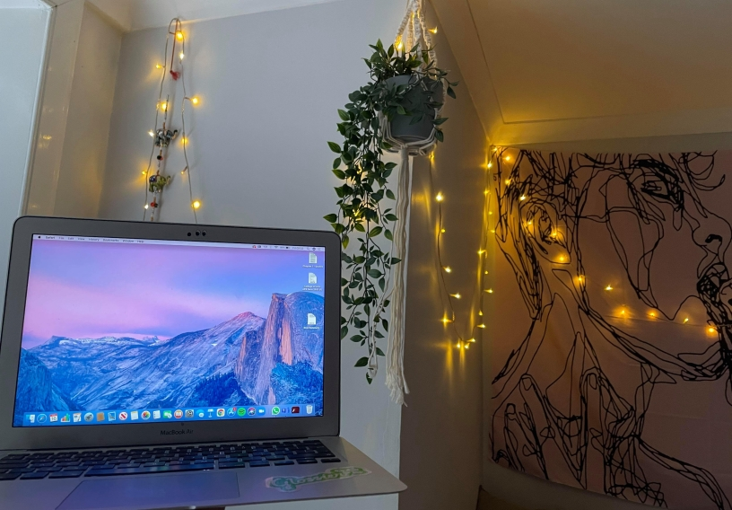 Laptop with macrame holder with plant, fairy lights and tapestry in backgrounbd.