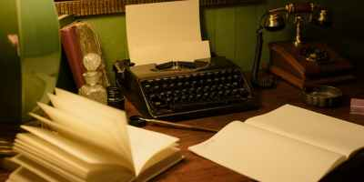 A dark wood desk against a green wall, with a green ceramic table lamp shining light on old books, a black typewriter, a rotary dial telephone, inkwell and pen. At the forefront of the desk are two open books, side-by-side, one mostly blank, as if in process of being written in with the pen and inkwell.